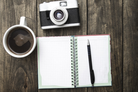 photo backgrounds: Vintage camera, diary with pan and cup pf coffee on wooden table.