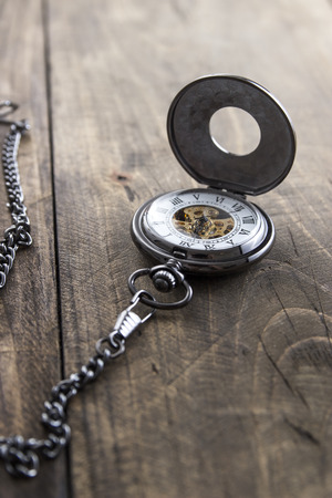 pocket watch on grunge wooden table, close up photo