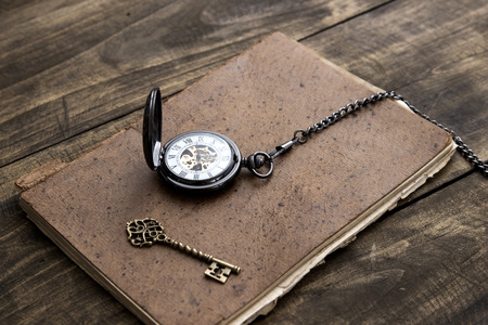 Antique book and pocket watch on grunge wooden table, close up photo