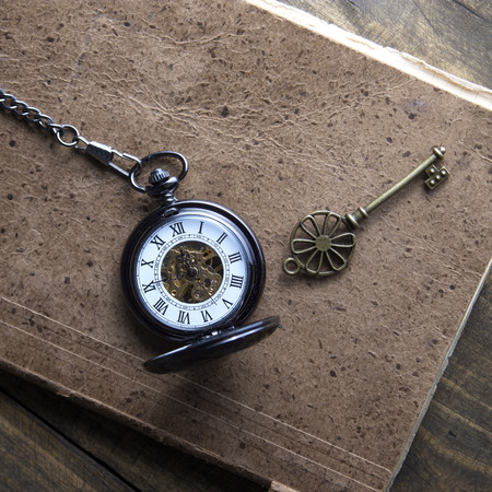 Antique book and pocket watch on grunge wooden table, from above photo