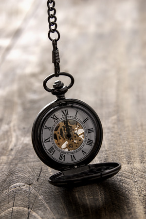 pocket watch over grunge wooden table, close up photo