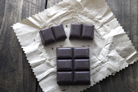 Noble dark chocolate on a wooden table, from above