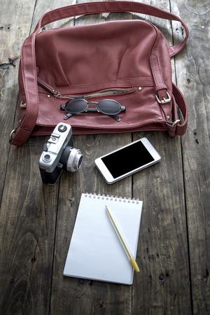 trivia: woman bag stuff, handbag over rustic wooden background