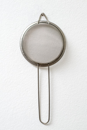 bolter: Strainer hanging against white wall as a background