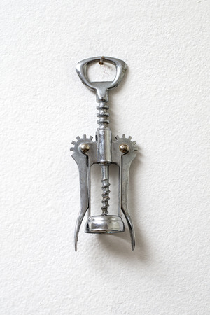 housewares: corkscrew hanging against white wall as a background