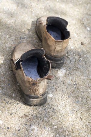 full of holes: Weathered forgotten shoes, outdoor with natural light Stock Photo