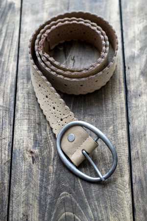 leather belt: leather belt on wooden table, close up