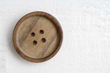 at button: button on a wooden table, from above