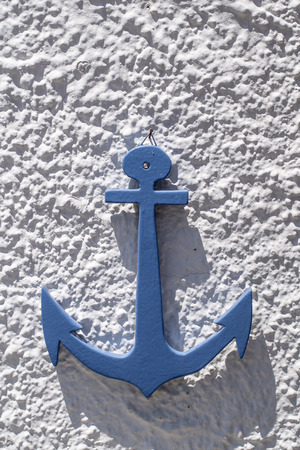water anchor: blue water anchor on the white wall, sunlight Stock Photo