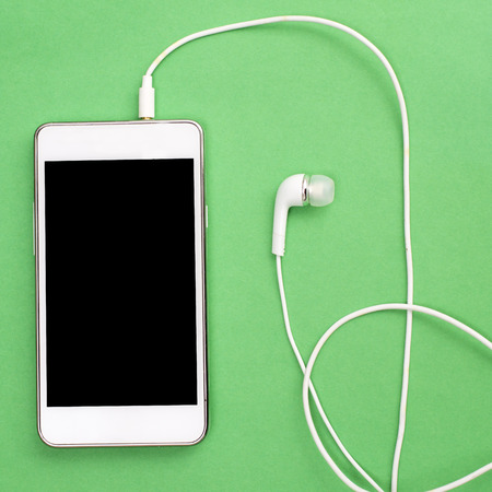 hear business call: White smart phone with earphones and isolated screen on green, from above