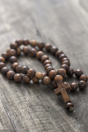 catholic symbol: Wooden rosary beads on old wooden background, close up Stock Photo