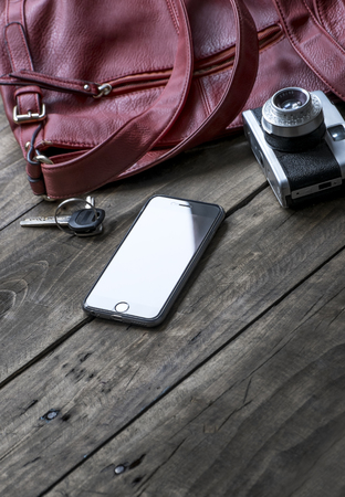 trivia: woman bag stuff, handbag over rustic wooden background,natural window light