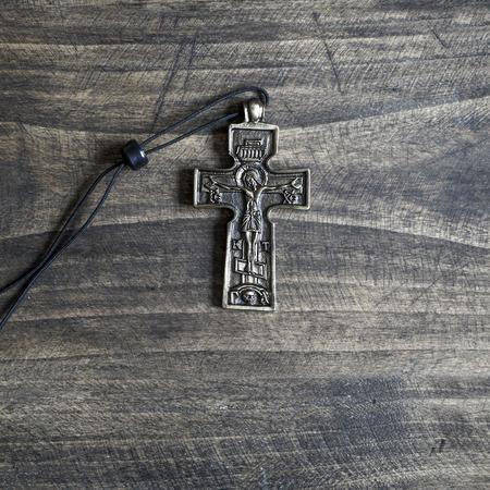 religion catolica: Primer sencillo collar de cruz cristiana en fondo de madera