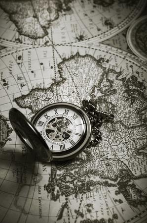 mapa conceptual: reloj de bolsillo antiguo de la vendimia en el viejo mapa de fondo, de cerca Foto de archivo