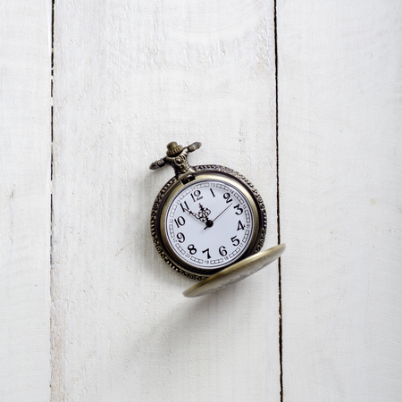 12 o'clock: antique  pocket watch with  chain against rustic aged wooden background with hands approaching twelve oclock