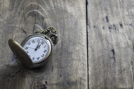 12 oclock: antique  pocket watch with  chain against rustic aged wooden background with hands approaching twelve oclock