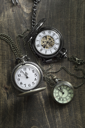 12 o'clock: Old pocket watches  on a rustic vintage wooden background