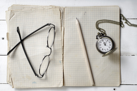 test deadline: Notebook with blank pages,  pen and vintage pocket watch on wooden background