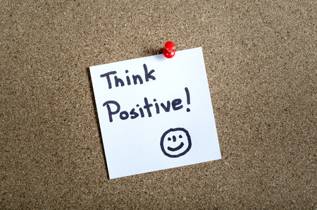 think positive - motivational slogan on a paper note