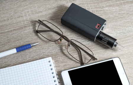 background e cigarette: Office desk table with notebooks, pen, smartphone and eye glasses. Top view Stock Photo