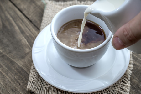 Pouring milk into a cup of coffee, close up Stock Photo