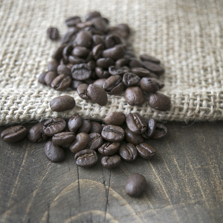 burlap sack: Close up of roasted coffee beans on a burlap sack Stock Photo