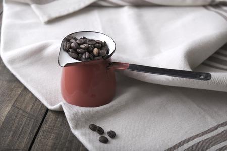 frijoles: Granos de caf� en una taza de esmalte en el fondo de madera