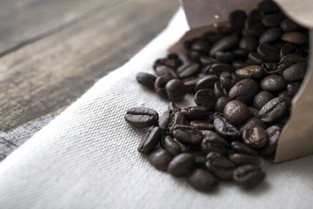 coffee crop: Close up of coffee beans on old table.