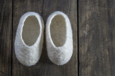 booties: Comfortable wool home Baby Booties on wooden background Stock Photo