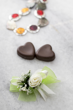 boutonniere: wedding boutonniere and hearth shaped chocolate on table Stock Photo