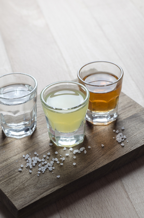 rakia: Glass of alcohol on wooden background close up