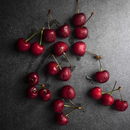 Cherries with waterdrops on table, from above Stock Photo