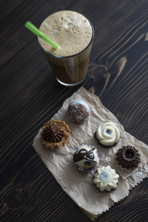Coffee and small colorful sweet cakes, from above
