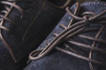 Close up of men's brogues made from blue oiled suede