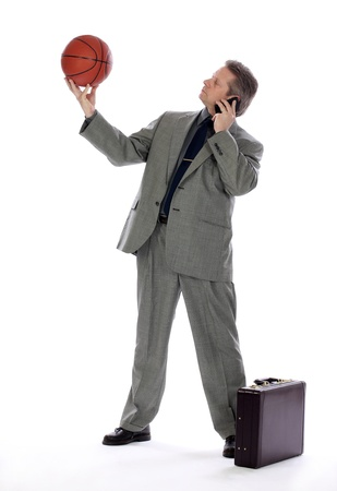 A man contemplates the game of basketball as he takes a business call Stock Photo