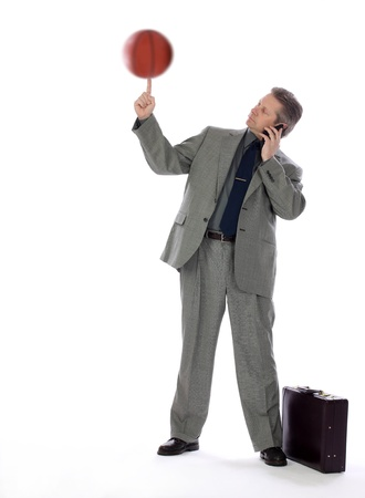 A business man spins a basketball on his finger showing multitasking skills