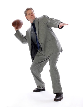 strategize: A businessman throwing a football aims for success with positive direction