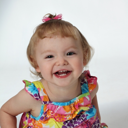A young girl shows her teeth with a big laugh and smile
