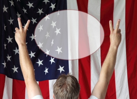 A man displays the peace sign toward the American flag