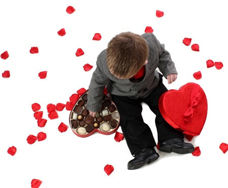 A young boy enjoys a box of valentine candy