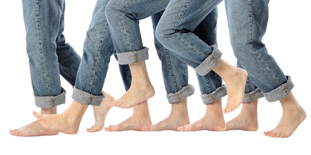 A womans bare feet advance one step forward in rolled up jeans on white