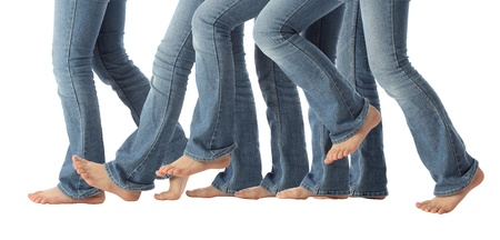 accomplish: A young girls bare feet advance one step forward in jeans on white