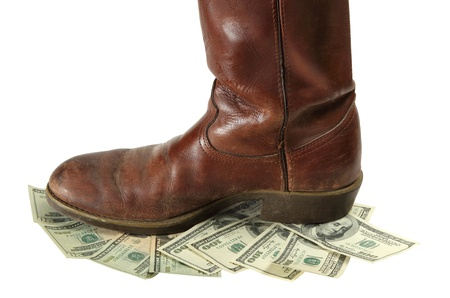 A boot stomps on money that is devalued and more worthless isolated on white Stock Photo