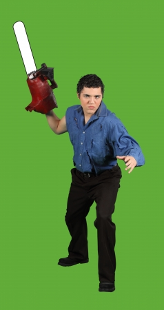 A psycho chainsaw murderer ready to attack isolated on green Stock Photo