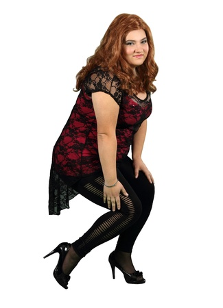 A girl in a red wig and black stockings isolated on white