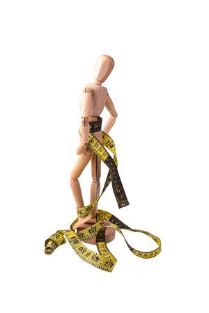 The wooden model of the person symbolizing a healthy slim figure with a measured tape round a waist Stock Photo
