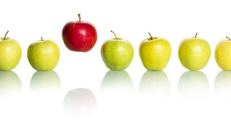 Manzana roja destacándose de la fila de manzanas verdes.