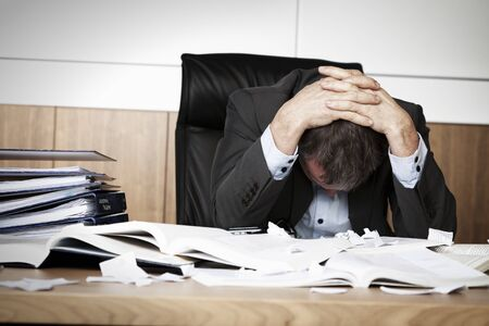 Worried businessman in dark suit sitting at office desk full with books and papers being overloaded with work. Imagens
