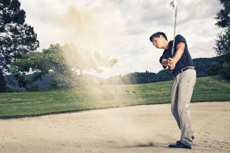 Golf player in sand trap.
