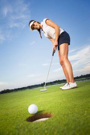 Glücklicher Mädchengolfspieler, der Ball in Loch einsetzt.